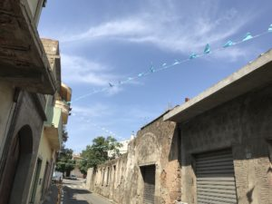 Blaue Wimpel auf Sardinien zwischen Häusern gespannt